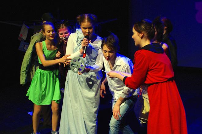 Ryhmä esiintymisasuisia nuoria ja filmikela.