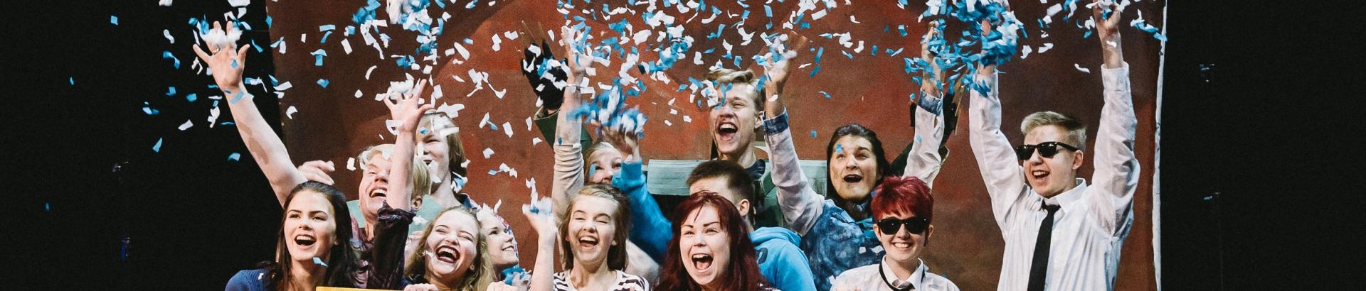 Ryhmä nuoria iloitsee kädet ilmassa.