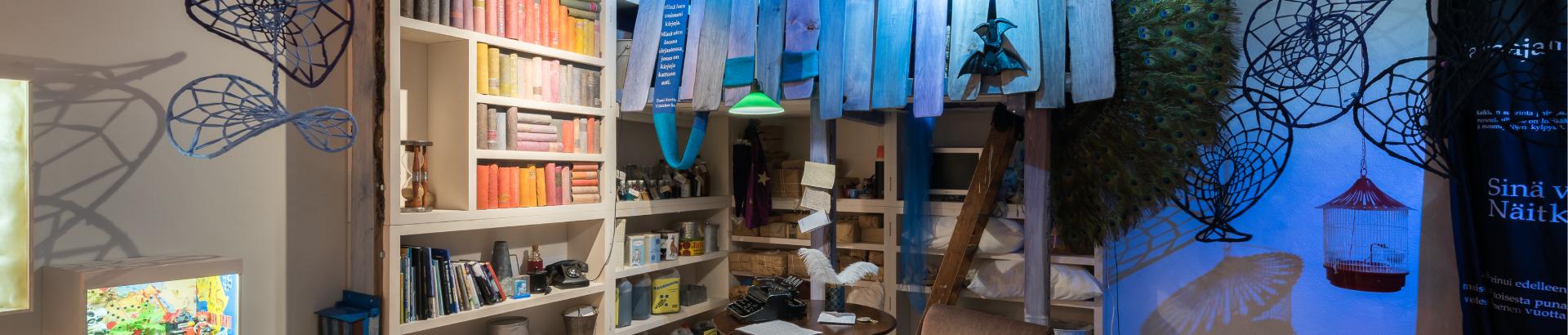 Unikudelmia-näyttelyn miljöötä kirjahyllyineen ja koristeineen.