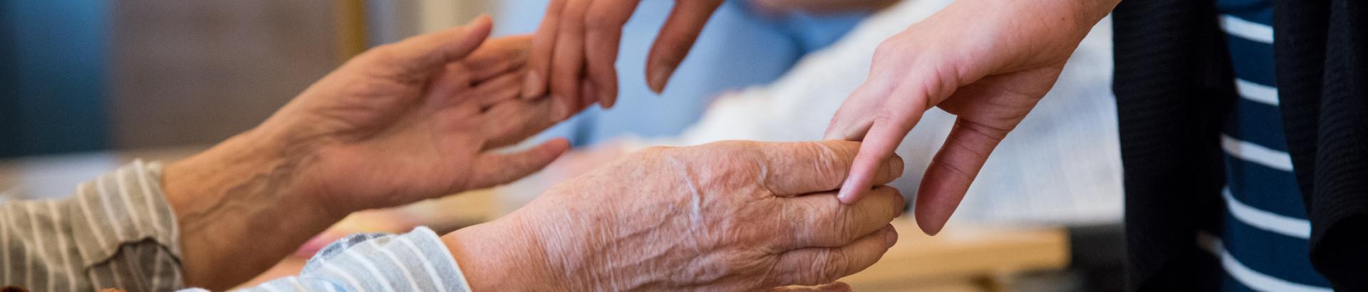 Koristekuva: kädet tarttuvat vanhuksen käsiin.